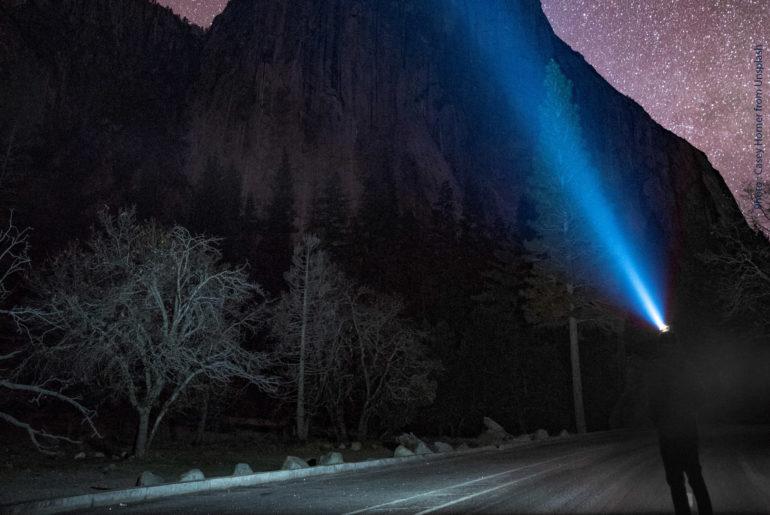 Looking at the night sky on the road with head lamp in front of a big dark mountain
